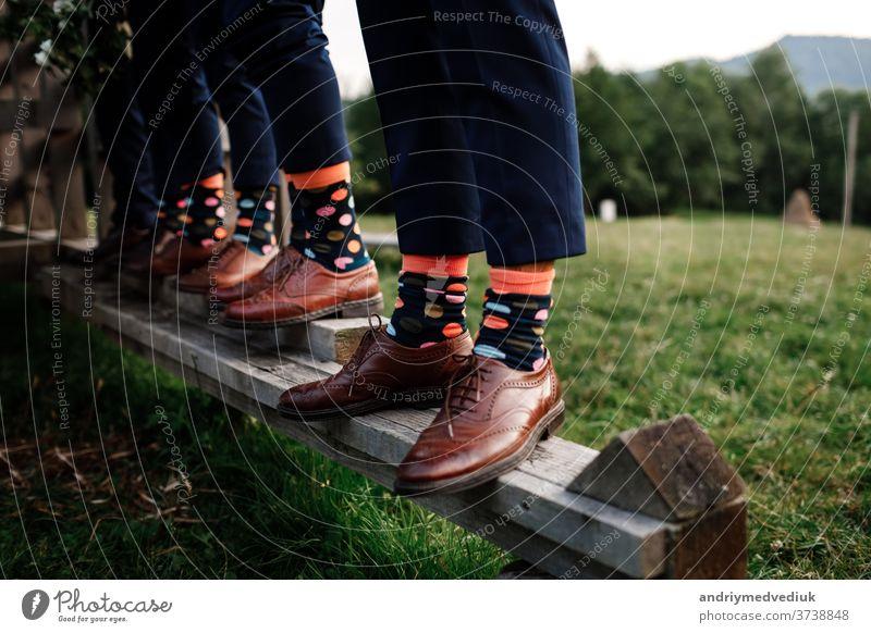 stilvolle Herrensocken. Stylischer Koffer, Herrenbeine, mehrfarbige Socken und neue Schuhe. Konzept von Stil, Mode, Schönheit und Urlaub Beine Kniestrümpfe