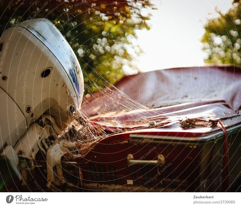 Motorboot mit Plane, Außenborder und Spinnennetz Boot Außenbordmotor Gegenlicht rot Licht Sonnenlicht Ruhe abgestellt friedlich unbenutzt Sommer Abdeckung