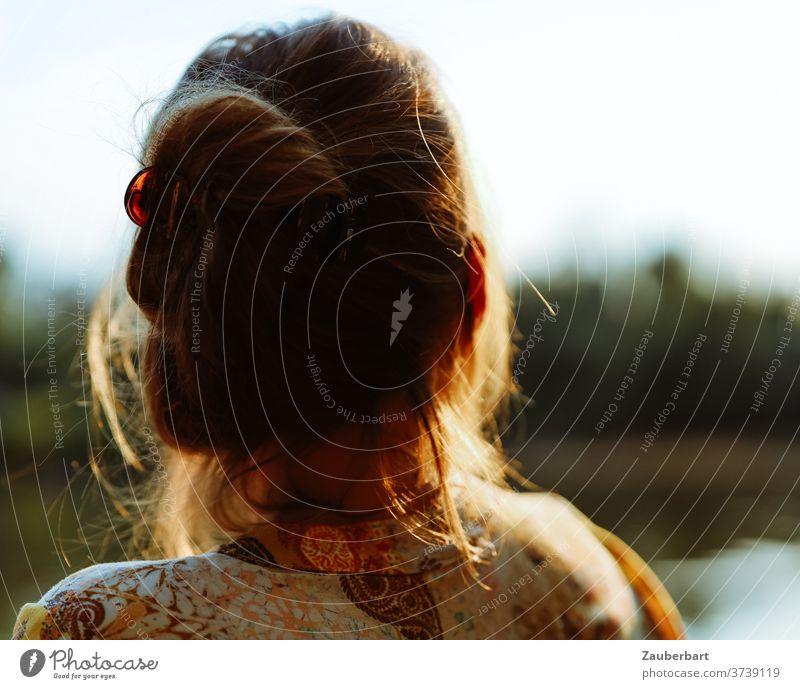 Kleine Auszeit - Kopf einer Frau im Gegenlicht, die über einen See schaut Haare Sonne schön Ruhe Frieden Entspannung Gedanken Pause gold Schein