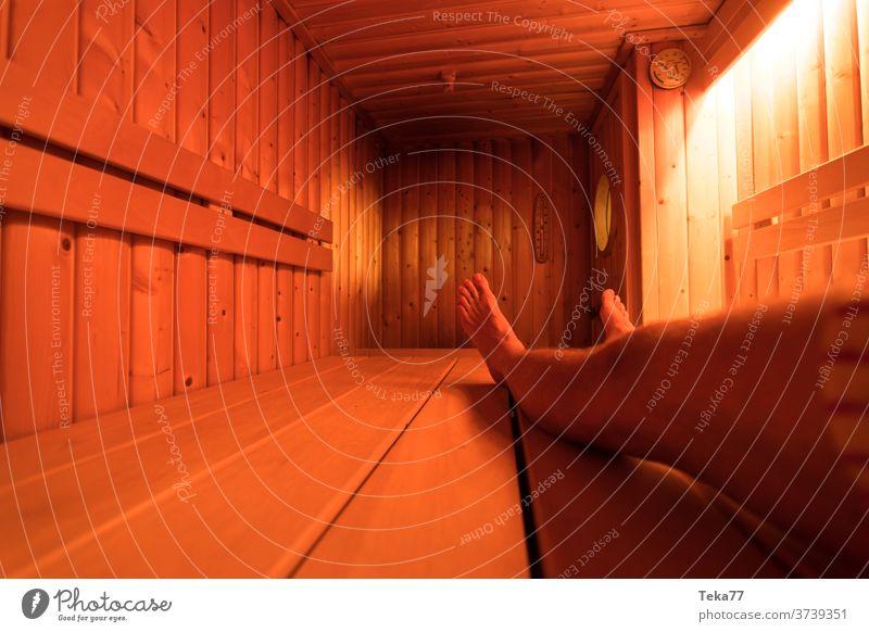 eine hölzerne Sauna von innen mit einem Mann beim Saunieren eine Sauna Holzsauna heiß warm moderne Sauna moderne Holzsauna Saunaofen Ofen Licht
