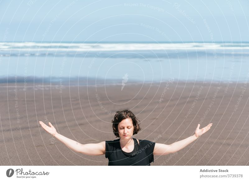 Schlanke Frau beim Meditieren am Strand Yoga MEER üben Asana Pose Augen geschlossen sitzen Gleichgewicht Windstille Meeresufer Harmonie Arme hochgezogen