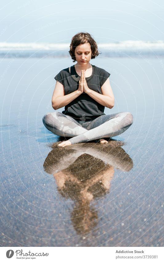 Schlanke Frau beim Meditieren am Strand Yoga MEER üben Asana Pose verdrehen Augen geschlossen sitzen Gleichgewicht Windstille Meeresufer Harmonie Wellness