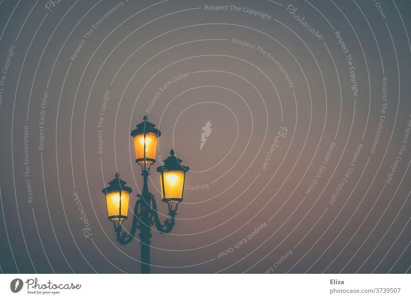 Eine altmodische Straßenlaterne leuchtet im Dunkeln Laterne nachts abends Licht Himmel Außenaufnahme Straßenbeleuchtung erhellen stimmungsvoll Lampe Beleuchtung