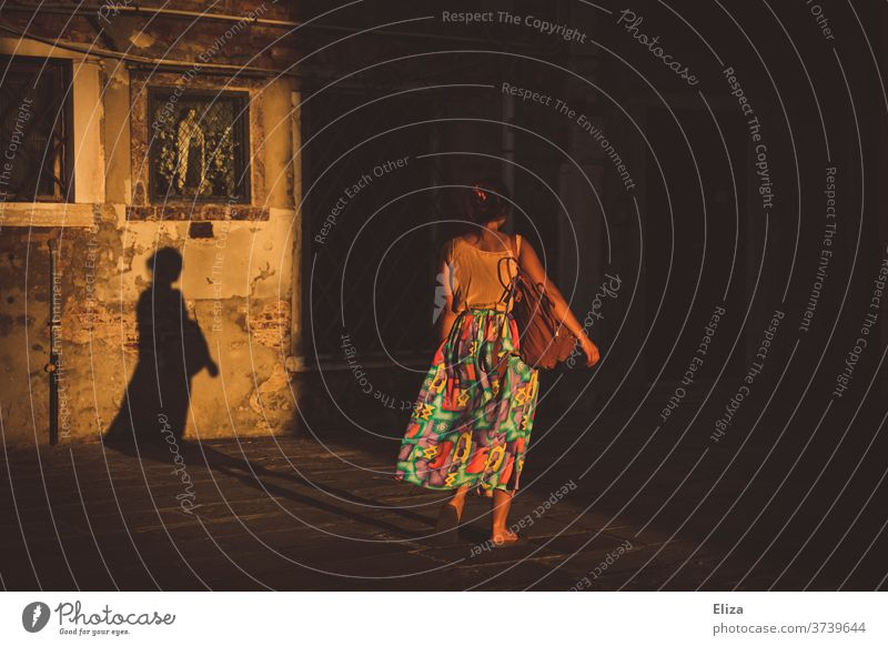 Eine Frau im Sonnenlicht wirft einen langen Schatten gehen Rückansicht von hinten Sommer bunt bunte Kleidung dunkel vergänglich davongehen Rock Altstadt