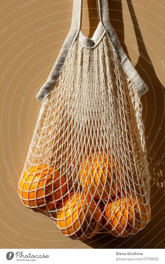 Reife Orangen in einem weißen Schnurbeutel. Beigefarbener Hintergrund. keine Verschwendung Öko kaufen orange Tasche beige wiederverwendbar Konzept Ökologie