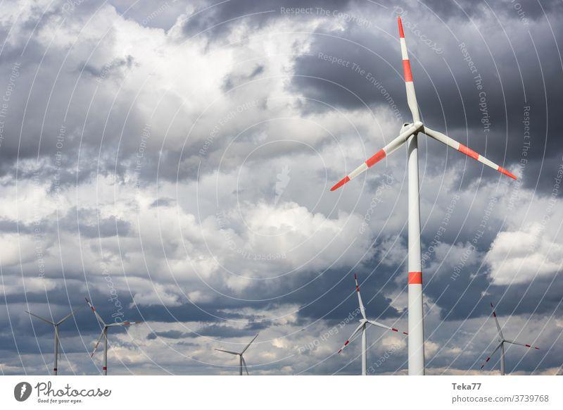 moderne Windräder vor bewölktem Sturmhimmel Windrad Windkraftanlage Windturbinen bewölkter Himmel Gewitterhimmel Wolken Gewitterwolken Ökostrom Windenergie