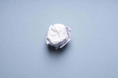 zerknüllte Papierkugel auf blauem Schreibtischunterlage Papierball Ball zerknülltes papier zerknittert verwerfen entsorgen Konzept scheitern Idee Müll