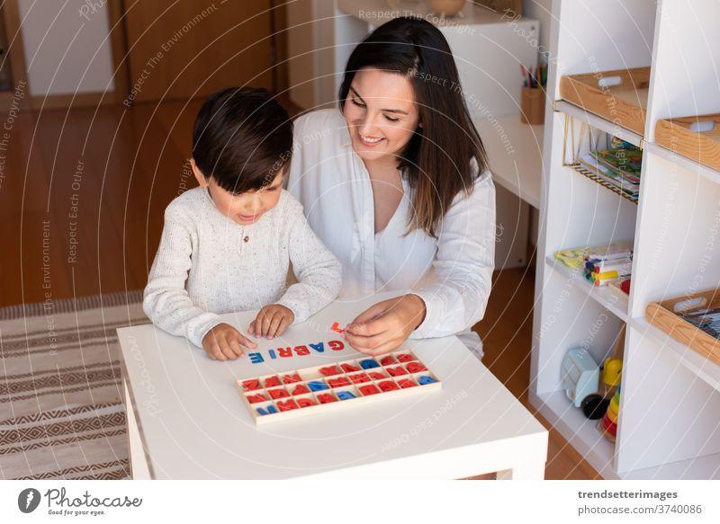 Das Kind lernt mit Hilfe eines Alphabets und der Mutter oder des Lehrers schreiben und lesen. Hausunterricht. Lernende Gemeinschaft. Montessori-Schule Briefe