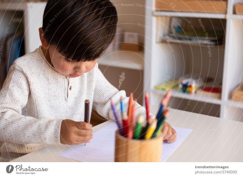 Kinder im Vorschulalter zeichnen mit Farbstiften. Hausunterricht. Lernende Gemeinschaft. Montessori-Schule. Kaukasier Schreibtisch Kinderzimmer Homeschooling