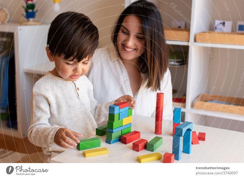Vorschulkind, das mit Holzklötzen spielt, und Hilfe eines Lehrer-Pädagogen. Hausunterricht. Lernende Gemeinschaft. Montessori-Schule Blöcke Holzspielzeug Spiel