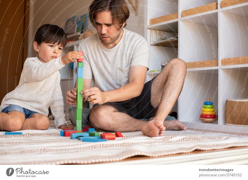 Kind und sein Vater spielen zu Hause mit Holzbausteinen. Heimunterricht. Bleiben Sie zu Hause. Zeit mit der Familie covid-19 sicher Coronavirus zu Hause bleiben