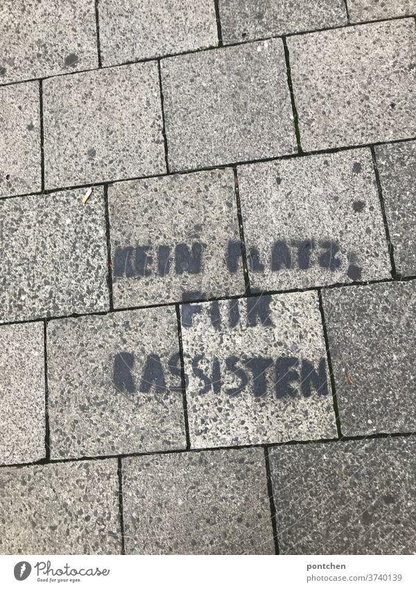 Kein Platz für rassisten steht auf Pflastersteinen am Boden. Botschaft, streetart. Antirassismus. Rassismus antirassismus botschaft widerstand politisch