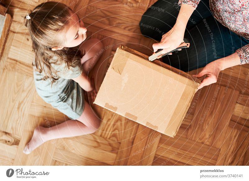 Frau beim Auspacken eines Pappkartonpakets im Zimmer zu Hause. Kleines Mädchen wartet auf das Öffnen eines Geschenks im Paket Ansicht Stock Klebeband Tochter
