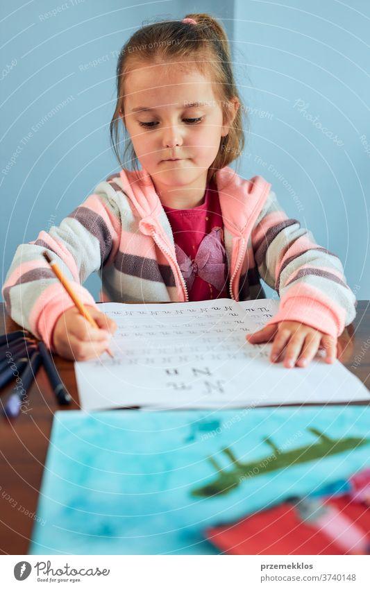 Kleines Mädchen im Vorschulalter, das in der Schule lernt, Briefe zu schreiben. Kleines Kind, das Briefe schreibt und eine Schularbeit schreibt. Konzept der Früherziehung
