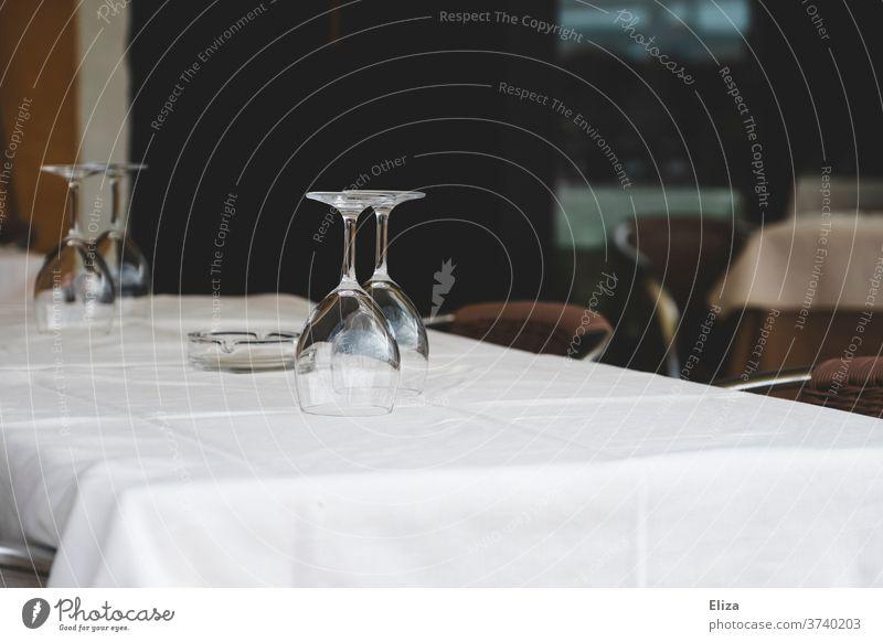 Zwei leere Weingläser warten auf einem Tisch in einem Restaurant auf ihre nächsten Gäste Tischdecke eingedeckt Gastronomie Straßencafé weiß draußen edel Paar