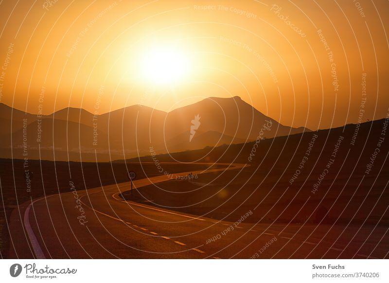 Auf der Kanarischen Insel Lanzarote führt diese Straße dem Sonnenuntergang entgegen zu den Vulkanen lanzarote vulkan straße sonnenuntergang gegenlicht lava