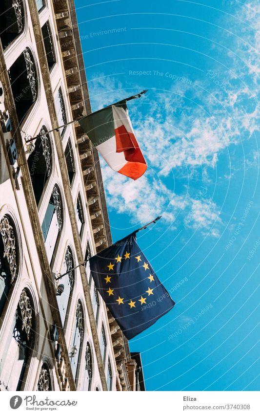 Eine italienische und eine europäische Flagge hängen nebeneinander an einem Gebäude und flattern im Wind Italien Europa Europaflagge gehisst Himmel Fahne
