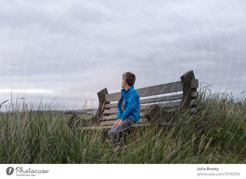 Junge auf einer Bank am Meer Seeküste MEER Meerblick wolkig Wolken Einsamkeit allein Gras Strandhafer Urlaub Pazifik Oregon Vereinigte Staaten Sommer cool