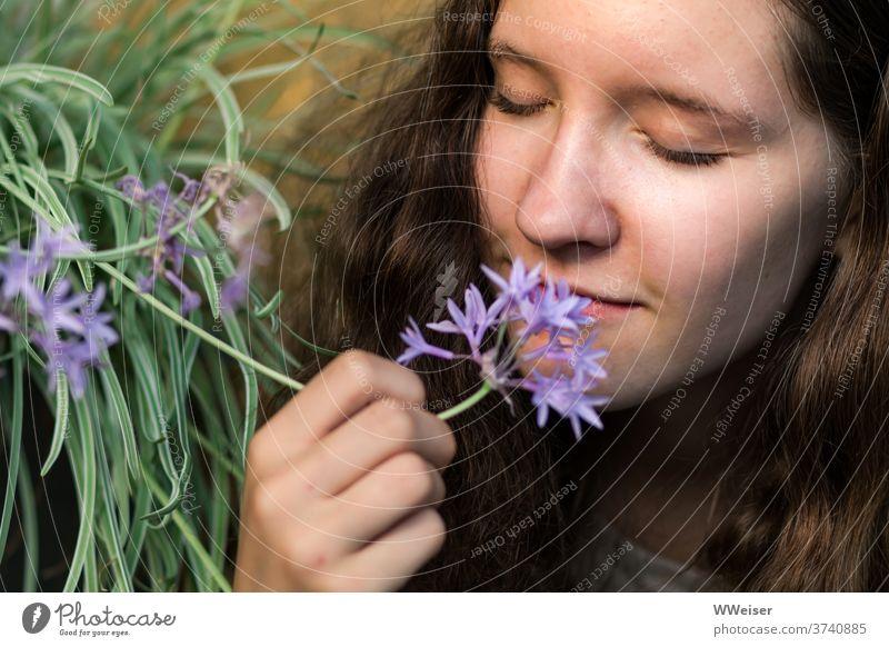 Junges Mädchen schnuppert genüsslich an der Knoblauchblume junge Frau riechen schnuppern Nase Duft Aroma Geruch intensiv Garten Blume natürlich Natur scharf