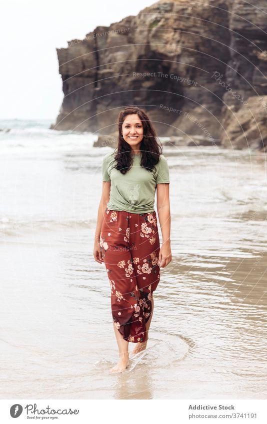 Lächelnde Frau am Strand im Sommer nass Meeresufer Spaziergang MEER Wasser Klippe Seeküste sich[Akk] entspannen reisen Tourismus Reisender Küste felsig Felsen