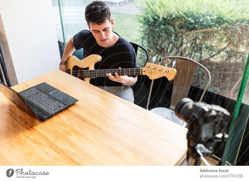 Junger Mann spielt Bassgitarre spielen Gitarre Musik stimmen Fähigkeit ausführen Musiker Instrument Klang Melodie Gesang Hobby jung männlich lernen Lifestyle