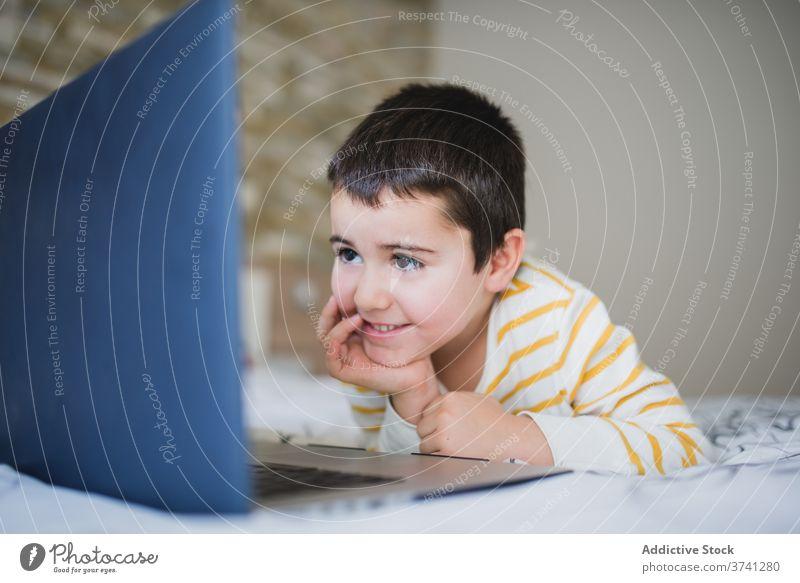 Kleines Kind verwendet Laptop zu Hause benutzend heimwärts wenig Apparatur Junge Browsen Schlafzimmer Surfen Internet Süchtige Gerät online Lifestyle männlich