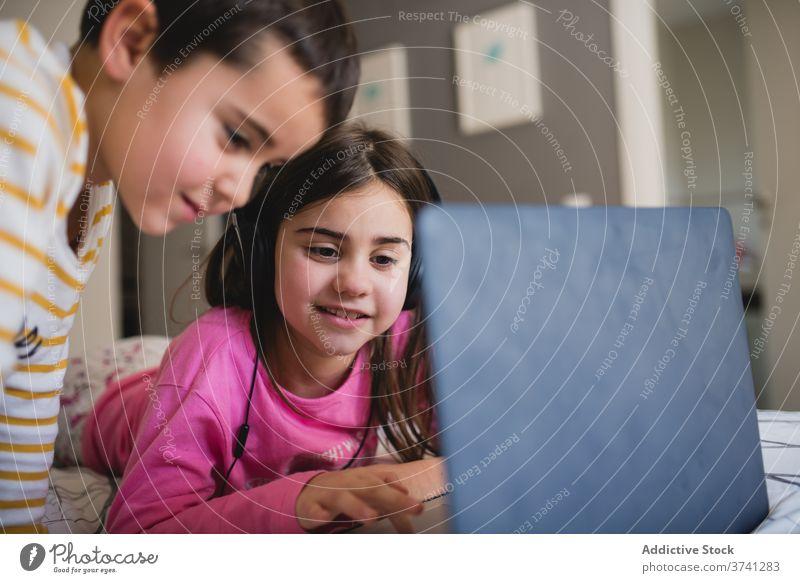 Fröhliche Kinder mit Laptop im Schlafzimmer Schwester und Bruder benutzend heimwärts Geschwisterkind Zusammensein wenig Apparatur heiter spielen Glück