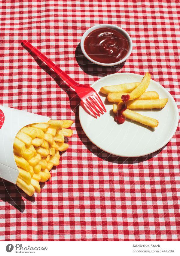 Pommes-Paket neben Teller mit in Ketchup getränkten Kartoffeln Amerikanische Kultur Gewürz Kartoffelchips ungesunde Ernährung roter Hintergrund weiß Fritten