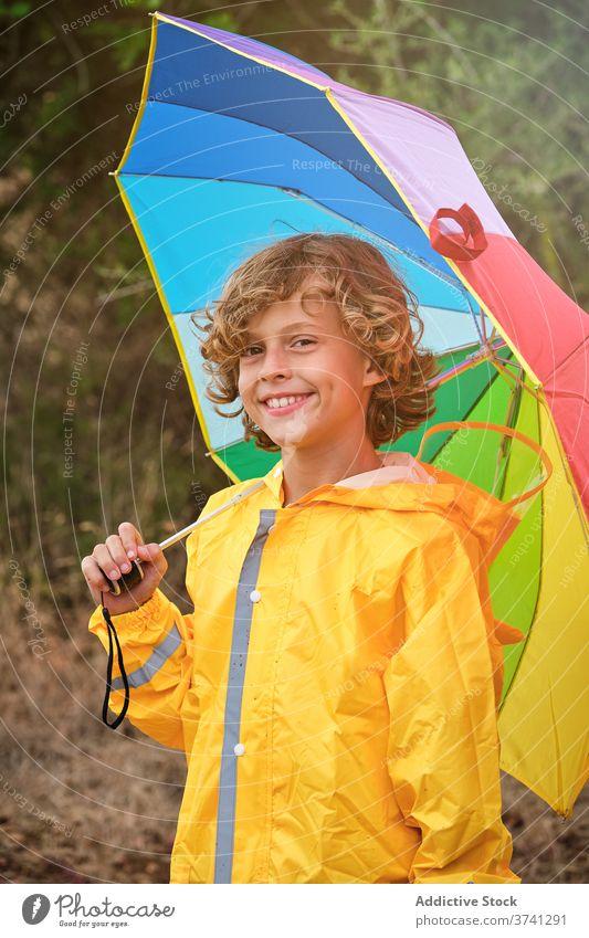 Junge im Regenmantel hält einen Regenschirm und lächelt in die Kamera Schuljunge gerade Pose Dusche Einstellung Regenbogen fallend Halt Gießen nass Wetter