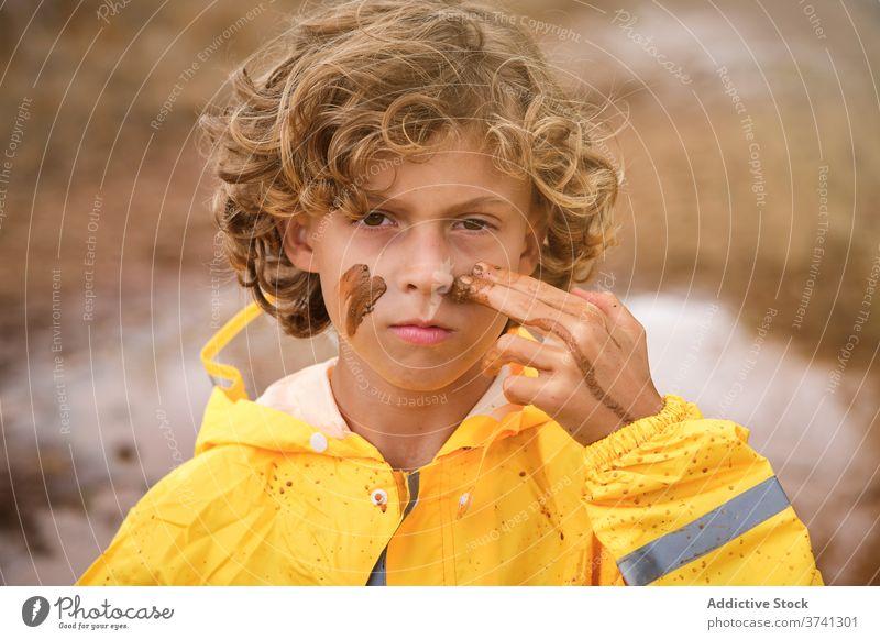Junge im Regenmantel Zeichnung Zeichen auf seinem Gesicht mit dem Schlamm mit Blick auf die Kamera ernst Witz Stolz Säugling unordentlich geistig spielerisch