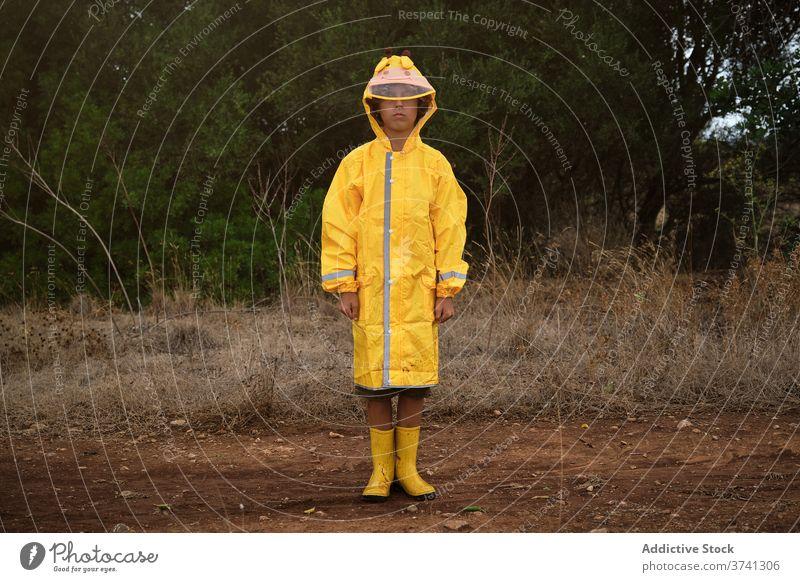 Porträt eines Jungen in einem gelben Regenmantel mit Kapuze und Regenstiefeln, der im Freien steht Schuljunge Tierhaut anhaben schützend stehen Weg bequem