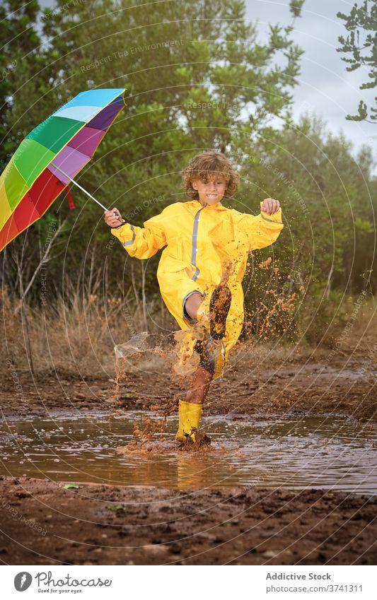Junge mit Stiefeln und Regenmantel hält einen Regenschirm und spielt in einer Pfütze Witz Schuljunge Dusche Einstellung Regenbogen lockig gestikulieren