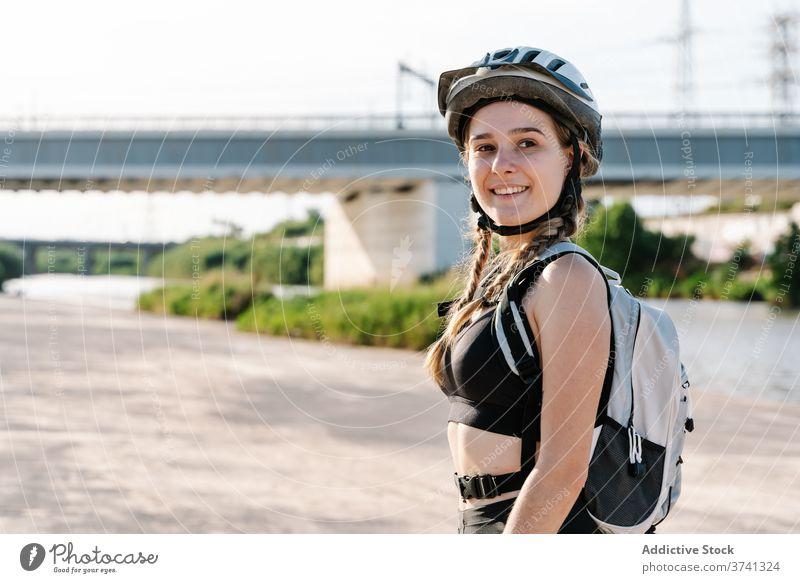 Porträt einer schlanken jungen Frau in Sportkleidung, die in die Kamera schaut Radfahrer sportlich Aktivität ruhen Schutzhelm Übung Flasche Biker Pause Durst