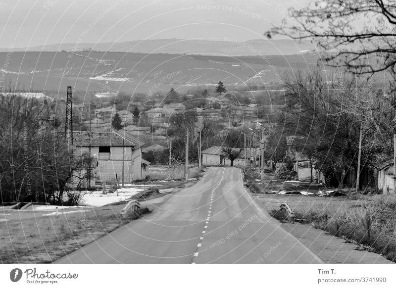eine Straße in Bulgarien s/w Schwarzweißfoto b&w b/w ruhig Einsamkeit Dorf Landschaft Januar Verkehr Allee Fahrt Autofahrt
