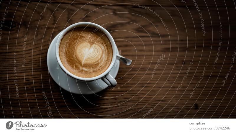 Cappuccino Love Liebe herzform aufschäumen zweig heissgetränk mitnehmen zum becher kreation kaffee cafe schaum muster milchschaum holztisch to go take away