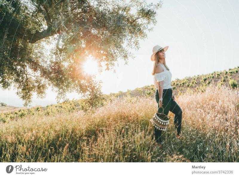 Junge Frau mit Strohhut und einem Korb, die im Sommer bei Sonnenuntergang durch das Feld geht. Konzept von Freiheit, Ruhe, Natur, Ökologie, grüner Welt und Glück.