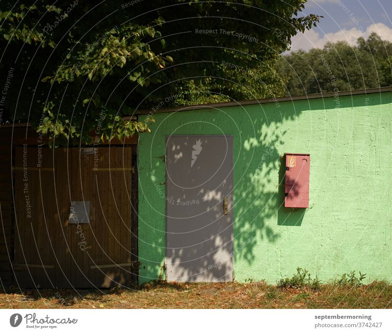 Garage mit Anbau altes Garagentor mit angeschlossenem seitlichen Gebäude. braue Tür grüne Fassade Feuerlöscher Baum Schattenbildung Sonnenlicht Wärme