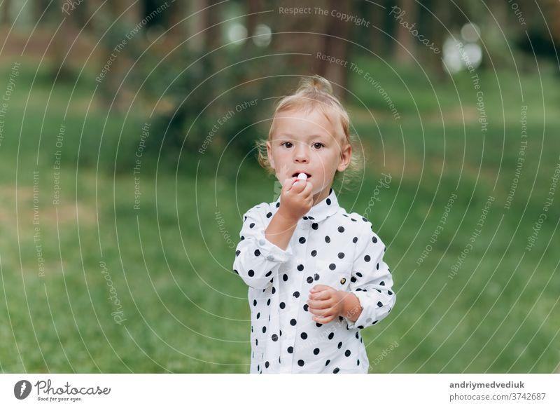 Das süße Mädchen schminkt sich mit Lippenstift und amüsiert sich im Wald, im Park. Das Konzept der Sommerferien, der Tag des Babys. Die Familie verbringt gemeinsam Zeit in der Natur.