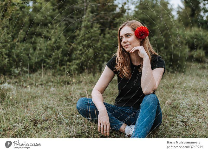 Junge schöne Frau mit Blume im Haar sitzt in der Natur attraktiv Hintergrund Schönheit blond Kaukasier niedlich Mode Behaarung Fröhlichkeit Glück Lifestyle