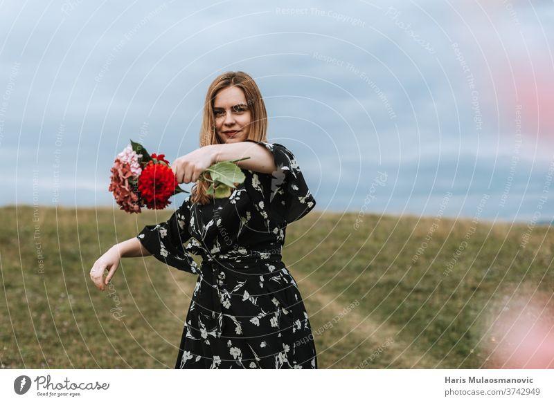 Frau hält Blumen im Freien in der Natur in der Hand Erwachsener attraktiv schön Schönheit niedlich Kleid Gesicht Mode Feld Blumenkranz Freiheit Mädchen Gras