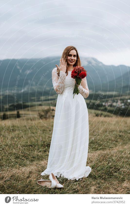Schöne Braut im Brautkleid, den Ring an der Hand haltend, draussen in der Natur Erwachsener attraktiv Hintergrund schön Schönheit Blumenstrauß hochzeitlich