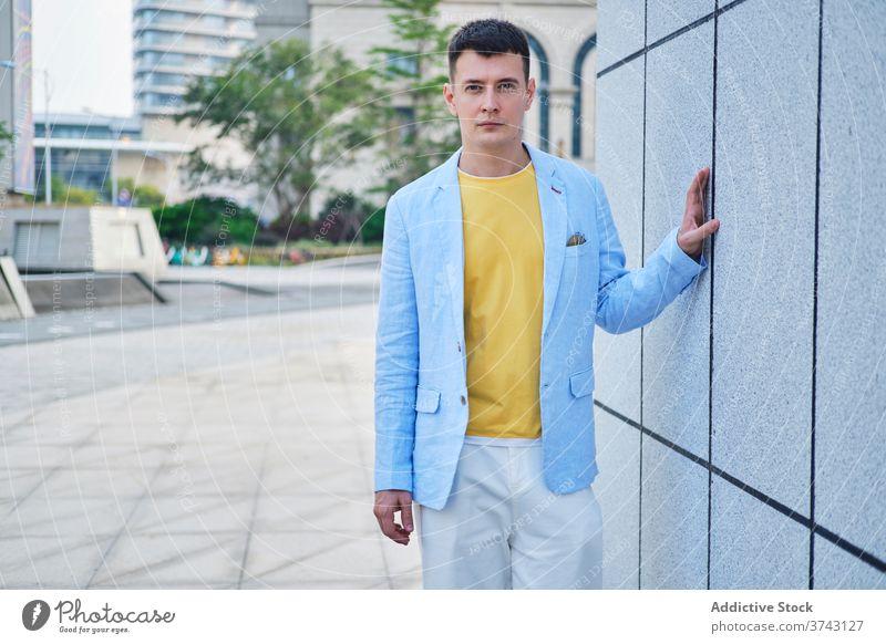 Junger Mann auf der Straße lehnt an der Wand und schaut in die Kamera Erwachsener Porträt Hintergrund blau gelb männlich einsam sehr wenige Stimmung Sinn Stil
