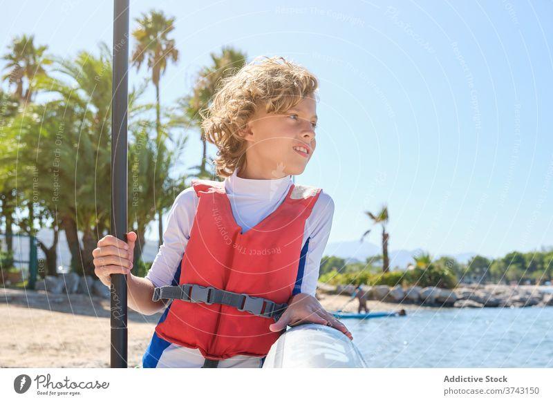 Abgelenkter Junge mit Weste, der sich an ein Paddel-Surfbrett lehnt und den Paddelstock hält retten Übung Kind Outfit Surfen Ruhe trainiert. behüten schützend