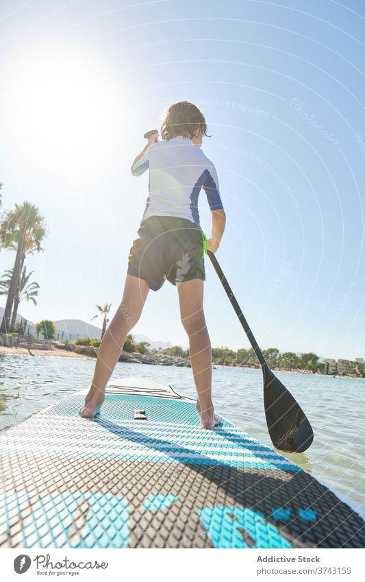 Vertikale Foto eines Kindes in seinem Rücken stehend auf einem Paddel Surfbrett Rudern in der Mitte des Meeres Lebensstile Surfen Fuß ruhig passen Erholung