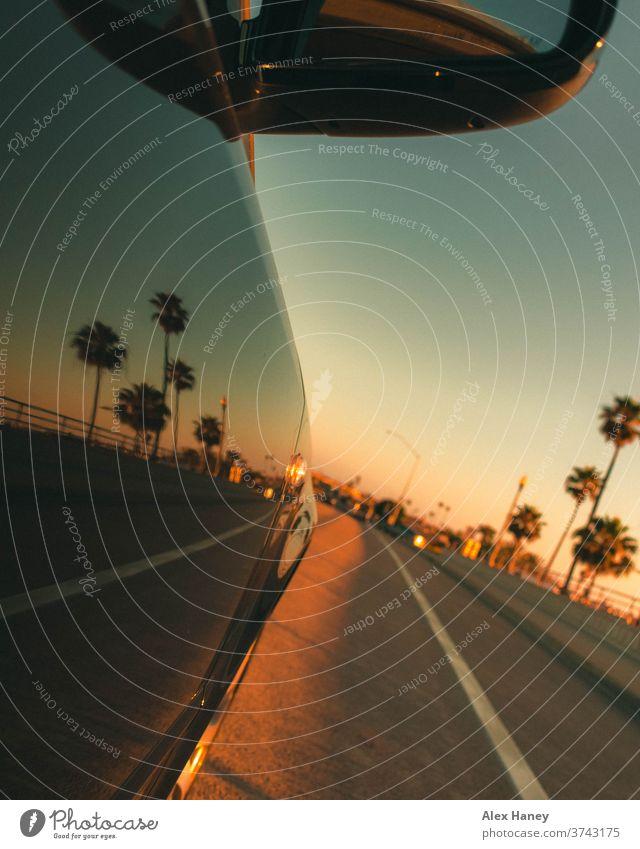 Ein Auto, das bei Sonnenuntergang mit Palmen im Hintergrund fährt PKW Kalifornien Orange County Reflexion & Spiegelung