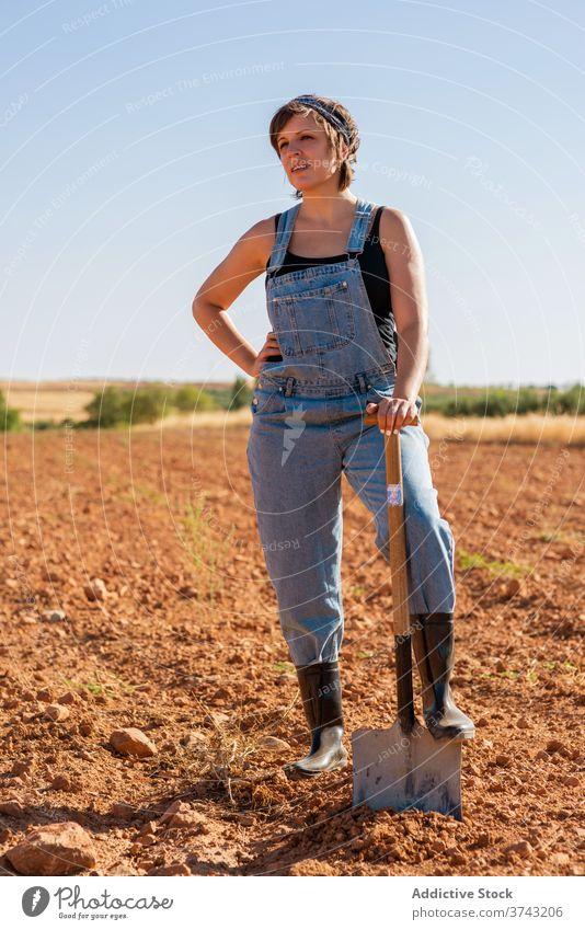Frau bei der Arbeit auf dem Feld in ländlicher Umgebung Landwirt Harke Sonnenhut Dorf Sommer Landschaft Ackerbau Natur Bauernhof Schonung Saison Umwelt tagsüber