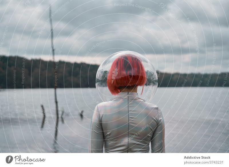 Frau im Astronautenanzug läuft auf Wasser futuristisch Raum Schutzhelm Anzug Fluss Natur Kosmonaut Konzept Silber Zukunft Phantasie Wissenschaft erkunden Planet