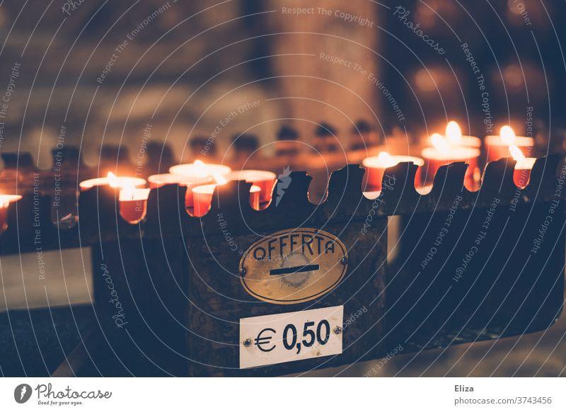 Brennende Opferkerzen, die gegen eine Spende von 50 Cent in einer italienischen Kirche angezündet werden Kerzen kosten 50cent 50 cent Geld Gedenken Trauer