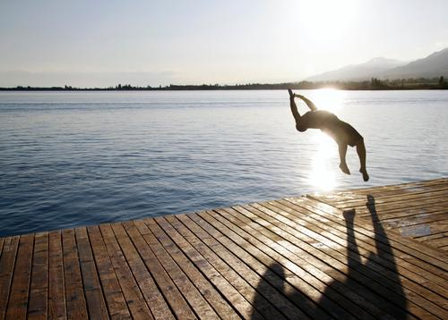 Ein junger Mann springt am Issyk-Kul-See in Kirgisistan ins Wasser Sommer Freiheit Jugend issyk kul springen springend Pier Freude