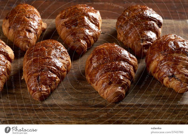 gebackene Croissants auf einem braunen Holzbrett, köstliches und appetitliches Gebäck Kruste Küche lecker Dessert Teigwaren Lebensmittel Französisch frisch